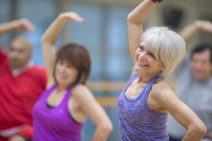 A multi-ethnic group of mature adults are taking an exercise class together at the gym. They are wearing athletic clothing and are working out.