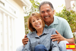 A close-up of a smiling senior couple.  The man and woman are wearing light blue shirts and are seated.  The woman is in front of the man, and the man's hands are embracing her shoulders.  Out-of-focus bushes are visible in the background.