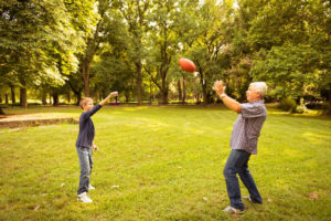 Grandson and grandfather play football in park