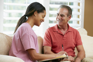 Nurse Discussing Records With Senior Male Patient During Home Visit Writing Notes Smiling