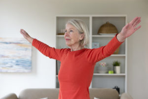Senior woman exercising in her living room. She has her arms outstretched.
