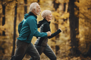 Closeup side view of a senior couple jogging in a forest and having fun. They are running on a winding forest road, laughing and doing their healthy routine. Trees in background have turned orange and yellow.