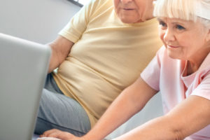Senior man and woman exercise together indoors watching training tutorial on a laptop concentrated