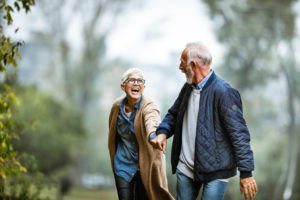 Cheerful senior couple having fun in the park. Focus is on woman. Copy space.