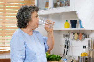 Senior asian woman drinking water while standing by window in kitchen background, people and healthy lifestyles